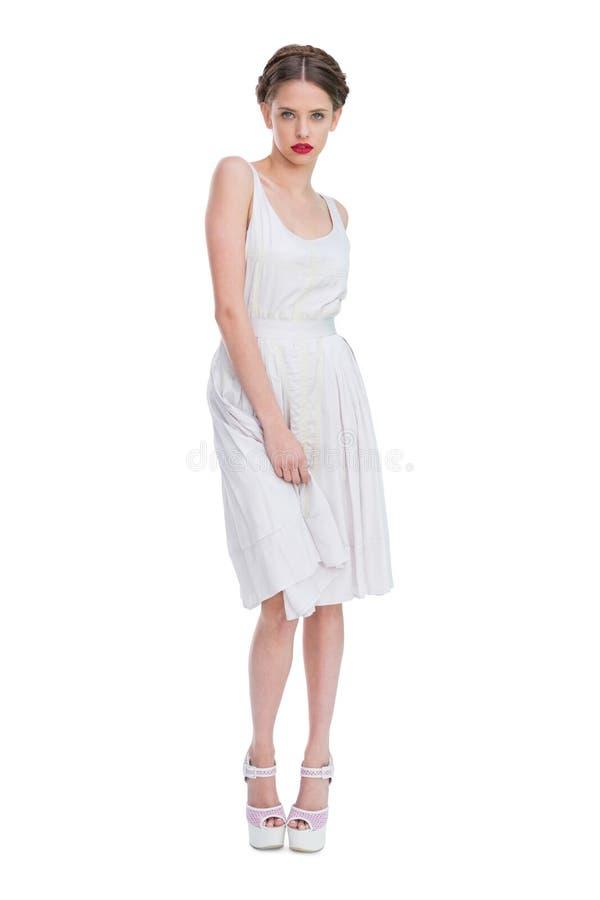 Ελκυστική γυναίκα που φορά την άσπρη στάση θερινών φορεμάτων στοκ εικόνες