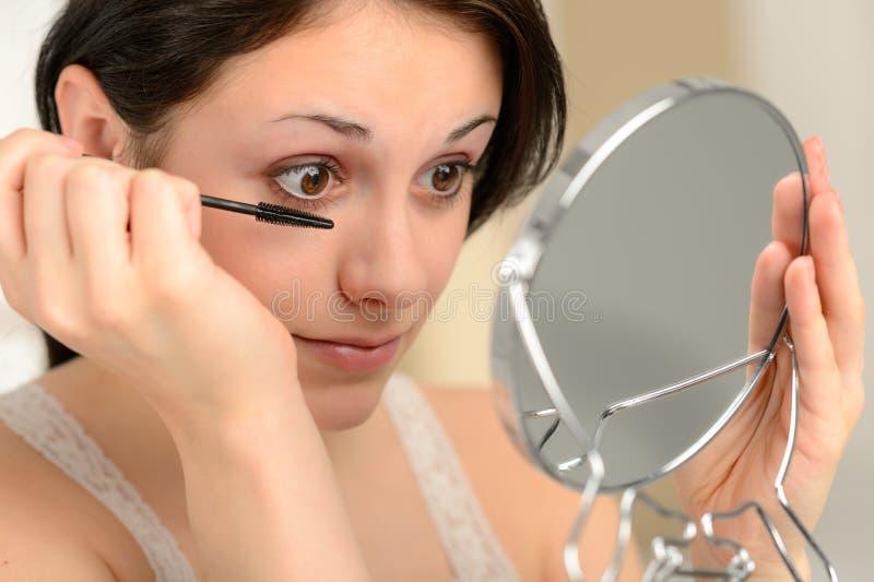 Ελκυστική γυναίκα που χρησιμοποιεί mascara και το φορητό καθρέφτη στοκ φωτογραφία