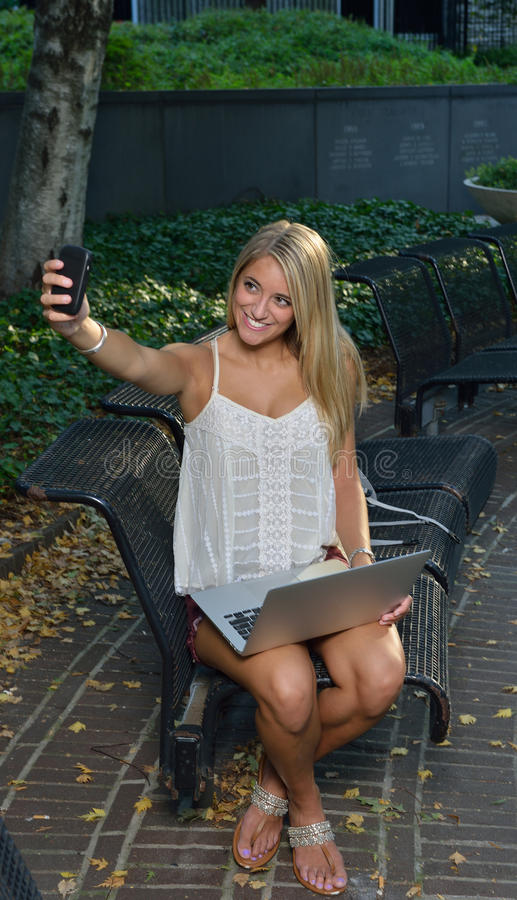 Ελκυστική γυναίκα σπουδαστής στην πανεπιστημιούπολη - παίρνει ένα selfie στοκ εικόνες