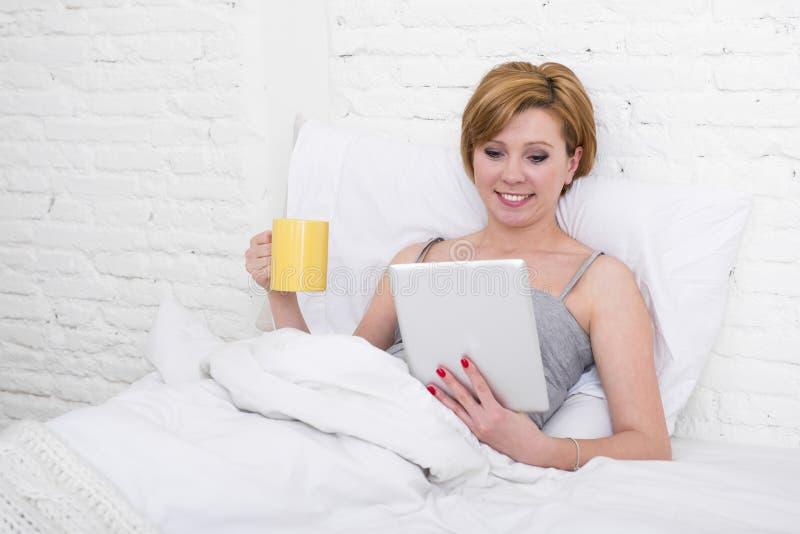 Ελκυστική γυναίκα στο κρεβάτι που χρησιμοποιεί τις ψηφιακές σε απευθείας σύνδεση ειδήσεις πρωινού ανάγνωσης μαξιλαριών ταμπλετών  στοκ εικόνα με δικαίωμα ελεύθερης χρήσης