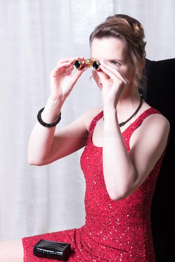 Ελκυστική γυναίκα στο κόκκινο φόρεμα που φαίνεται ενίσχυση γουρνών - γυαλί στοκ φωτογραφίες
