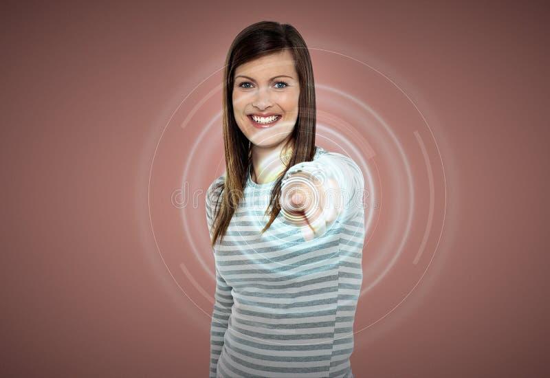Ελκυστική γυναίκα σχετικά με την εικονική οθόνη στοκ εικόνα