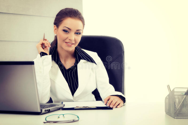Ελκυστική επιχειρηματίας που εργάζεται με το lap-top στο γραφείο στοκ εικόνα με δικαίωμα ελεύθερης χρήσης