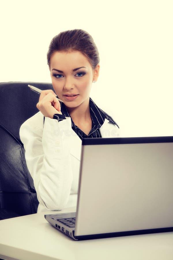 Ελκυστική επιχειρηματίας που εργάζεται με το lap-top στο γραφείο στοκ εικόνες