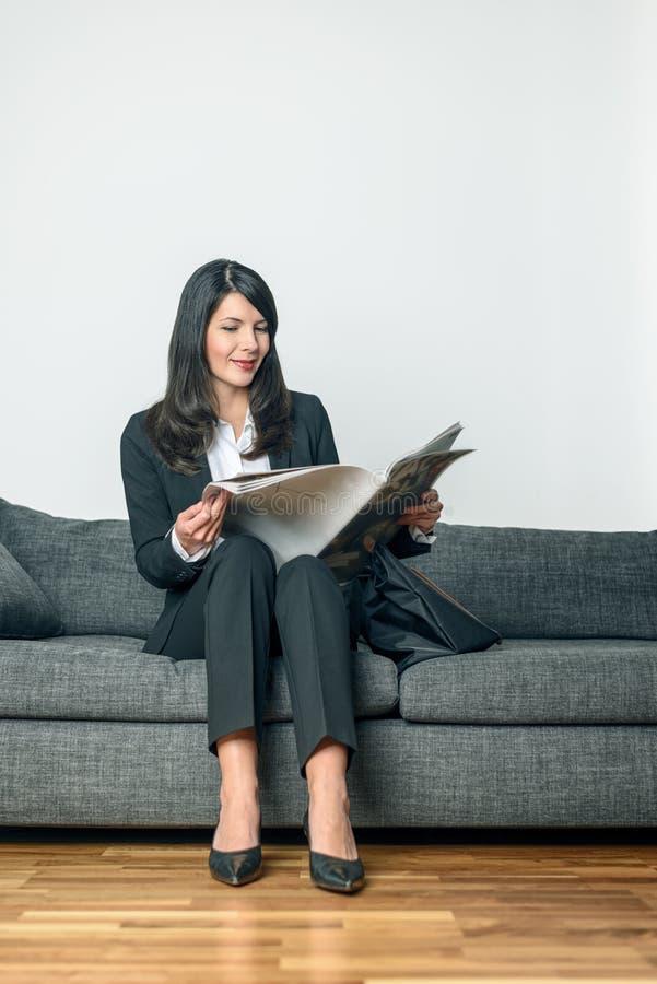 Ελκυστική επιχειρηματίας που διαβάζει μια εφημερίδα στοκ φωτογραφίες