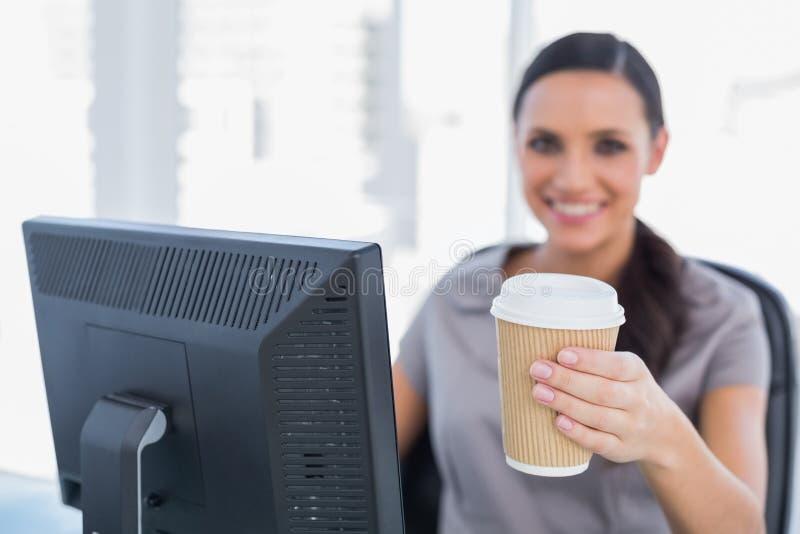 Ελκυστική επιχειρηματίας που προσφέρει τον καφέ στη κάμερα στοκ εικόνες