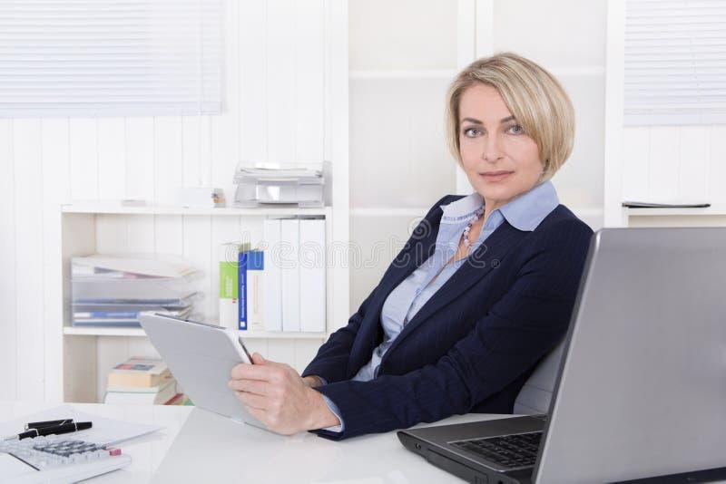 Ελκυστική ευτυχής ηλικιωμένη ή ανώτερη επιχειρησιακή γυναίκα στο γραφείο. στοκ εικόνες