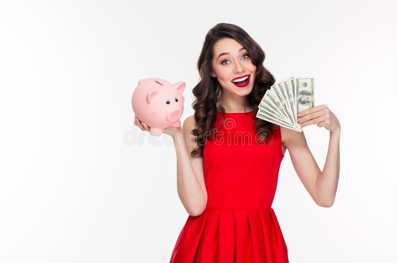 Ελκυστική ευτυχής νέα σγουρή γυναίκα που κρατά τη piggy τράπεζα και τα χρήματα στοκ φωτογραφία με δικαίωμα ελεύθερης χρήσης