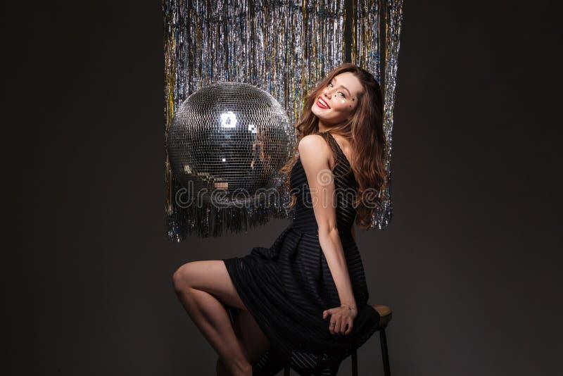 Ελκυστική εύθυμη νέα συνεδρίαση γυναικών κοντά στη σφαίρα disco στοκ εικόνα