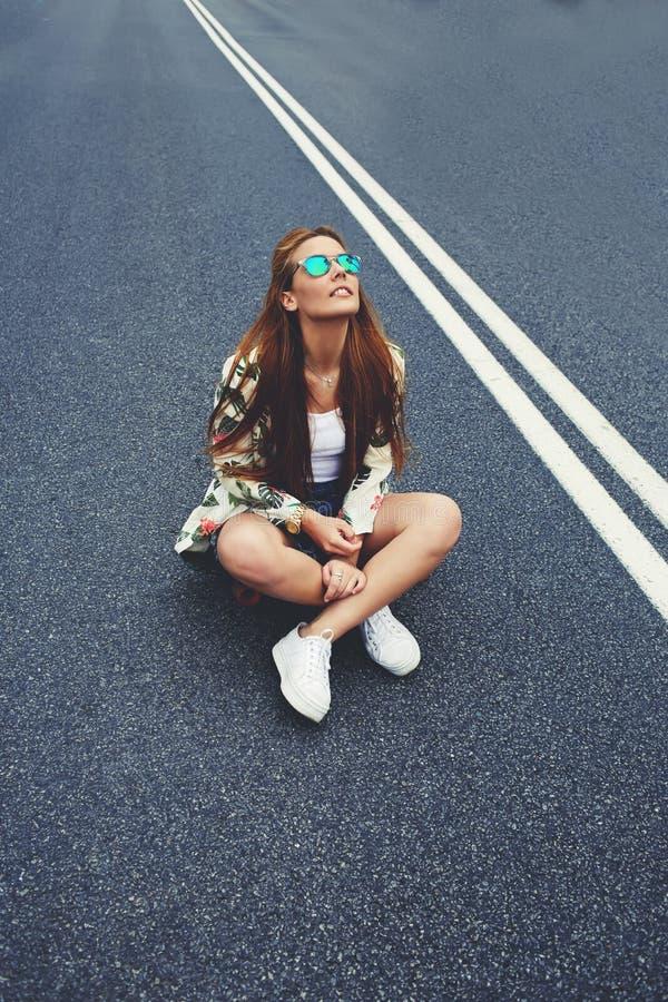 Ελκυστική καλιφορνέζικη συνεδρίαση κοριτσιών hipster στο ταχύπλοο σκάφος της longboard στη μέση του δρόμου ασφάλτου στοκ φωτογραφία με δικαίωμα ελεύθερης χρήσης
