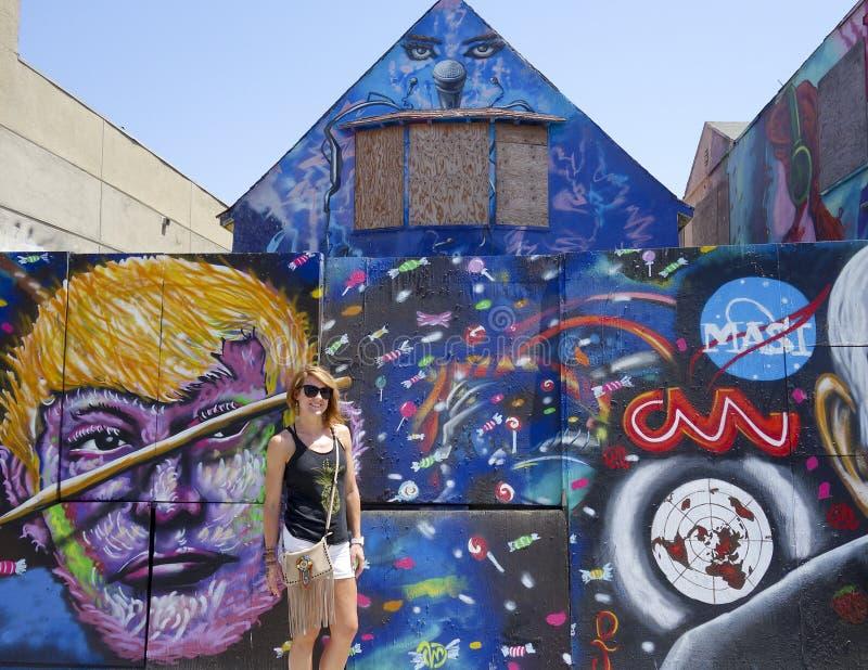 Ελκυστική κοκκινομάλλης γυναίκα μπροστά από μια ζωηρόχρωμη τοιχογραφία στοκ εικόνες