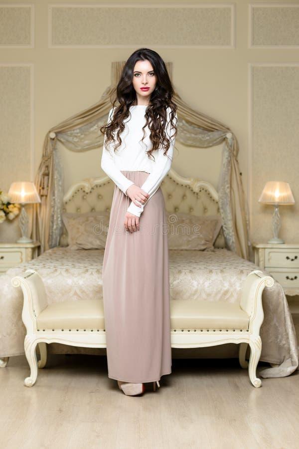 Ελκυστική κομψή νέα γυναίκα στο μακρύ φόρεμα στοκ εικόνες