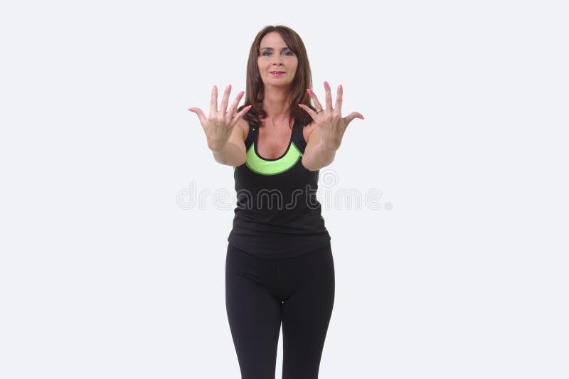 Ελκυστική μέσης ηλικίας γυναίκα στο αθλητικό εργαλείο που κρατά ψηλά δέκα δάχτυλα στοκ εικόνες