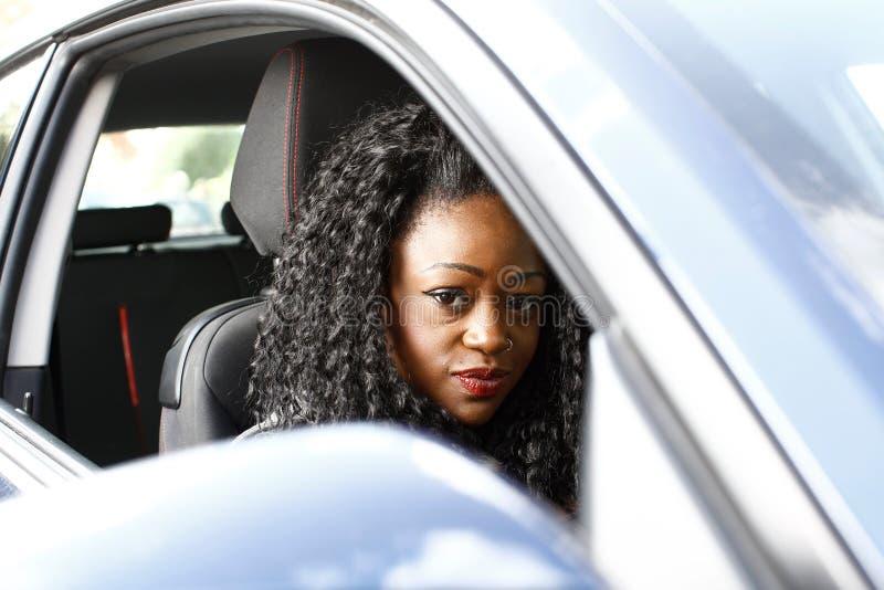 Ελκυστική μοντέρνη αφρικανική γυναίκα που οδηγεί ένα αυτοκίνητο στοκ εικόνες