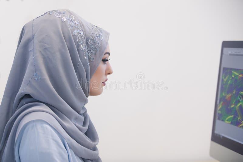 Ελκυστική μουσουλμανική νέα εργασία γυναικών στην αρχή στον υπολογιστή στοκ φωτογραφία