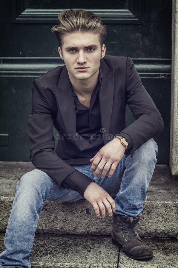 Ελκυστική μπλε eyed, ξανθή συνεδρίαση νεαρών άνδρων στα βήματα σκαλοπατιών στοκ φωτογραφίες με δικαίωμα ελεύθερης χρήσης