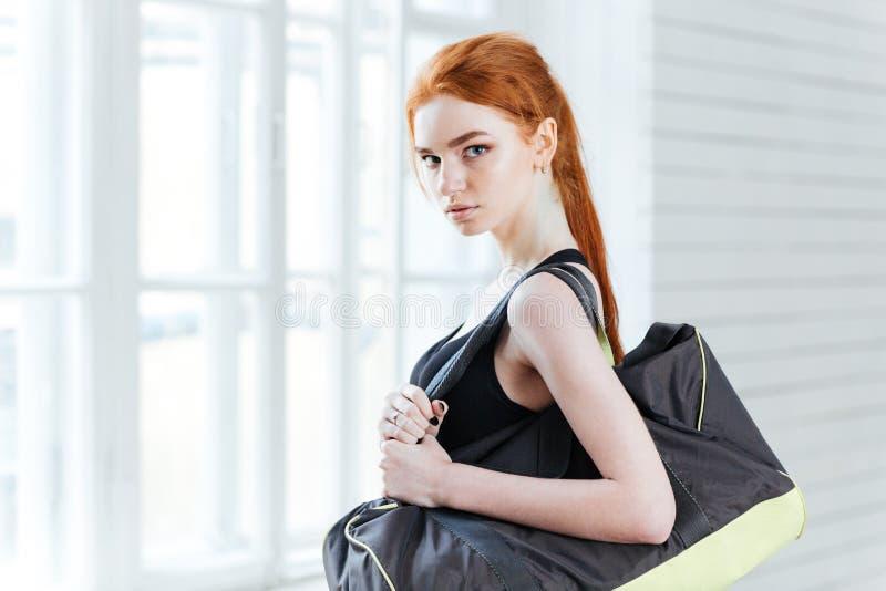 Ελκυστική νέα γυναίκα με το μπουκάλι νερό και την αθλητική τσάντα στοκ εικόνα