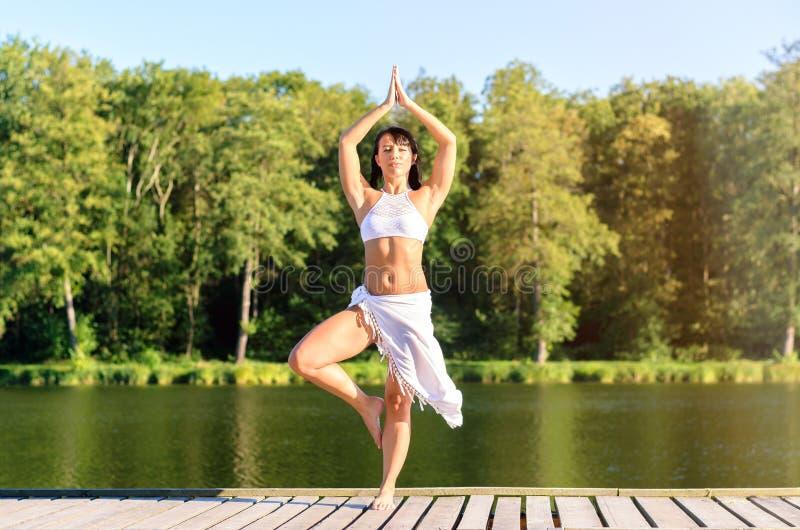 Ελκυστική νέα γυναίκα που κάνει τις ασκήσεις γιόγκας στοκ εικόνες