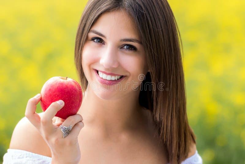 Ελκυστική νέα γυναίκα που κρατά το κόκκινο μήλο υπαίθρια στοκ εικόνα
