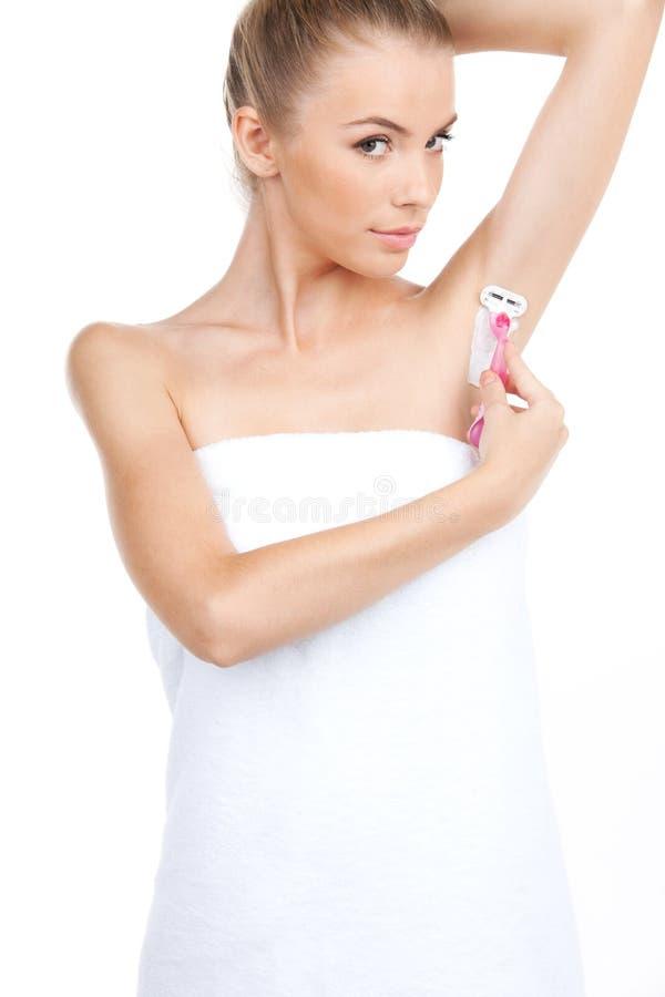 Ελκυστική νέα γυναίκα που ξυρίζει τις μασχάλες της στοκ εικόνα