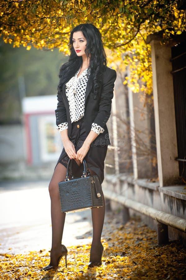 Ελκυστική νέα γυναίκα σε έναν φθινοπωρινό πυροβολισμό μόδας Όμορφη μοντέρνη κυρία στη γραπτή τοποθέτηση εξαρτήσεων στο πάρκο στοκ φωτογραφίες