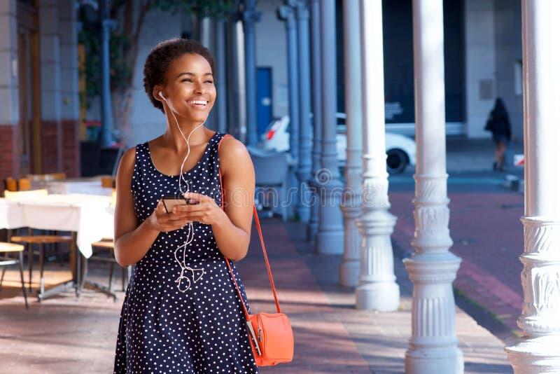 Ελκυστική νέα μαύρη γυναίκα που περπατά με το κινητό τηλέφωνο και τα ακουστικά στοκ φωτογραφία