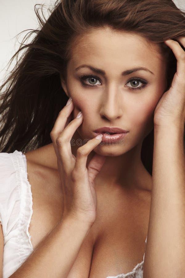 Ελκυστική νέα χαλάρωση γυναικών στο άσπρο υπόβαθρο στοκ φωτογραφίες με δικαίωμα ελεύθερης χρήσης