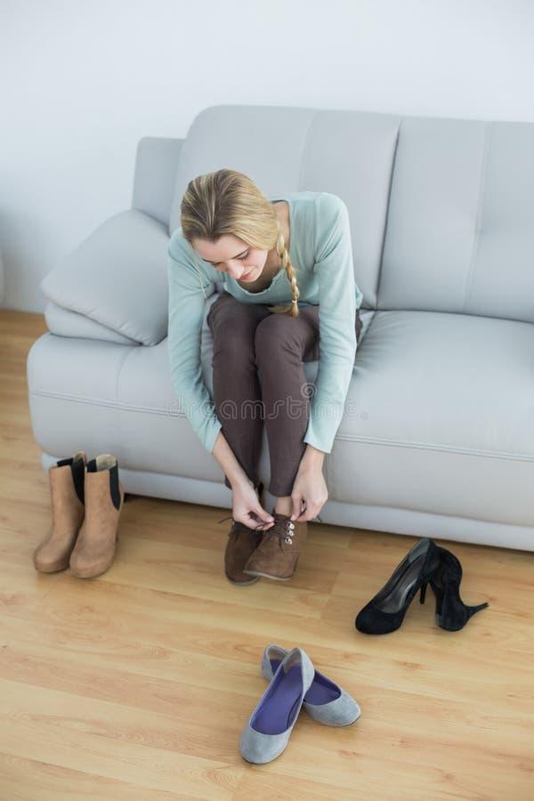 Ελκυστική ξανθή γυναίκα που δένει τα κορδόνια της που κάθονται στον καναπέ στοκ φωτογραφία
