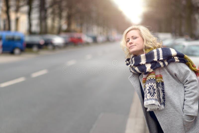 Ελκυστική ξανθή γυναίκα που περιμένει ένα αμάξι ή έναν ανελκυστήρα στοκ φωτογραφίες