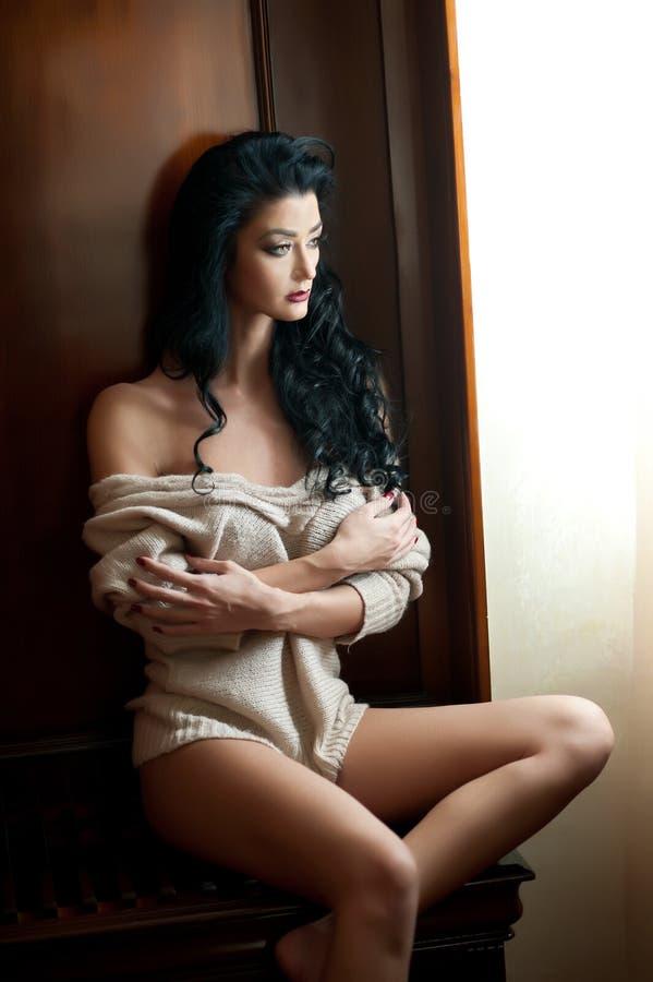 Ελκυστική προκλητική ημίγυμνη τοποθέτηση brunette provocatively στο πλαίσιο παραθύρων Πορτρέτο της αισθησιακής γυναίκας στην κλασ στοκ εικόνα