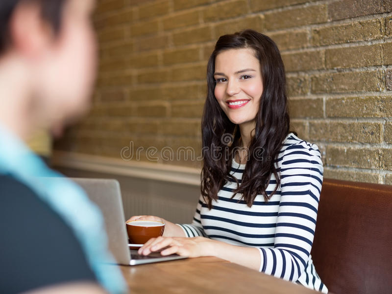 Ελκυστική συνεδρίαση γυναικών με το lap-top στον πίνακα στοκ εικόνες