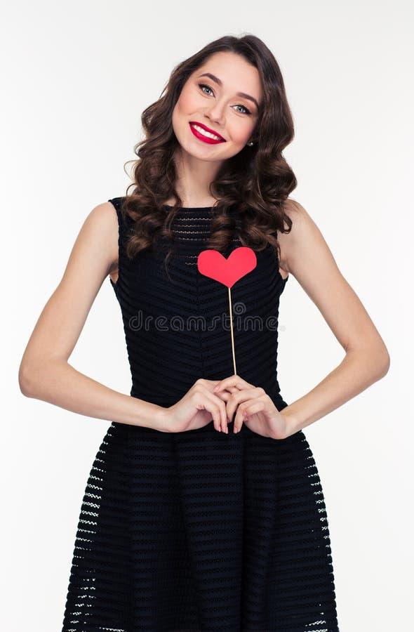 Ελκυστική χαμογελώντας γυναίκα στο αναδρομικό ύφος που στέκεται με τα στηρίγματα καρδιών στοκ φωτογραφίες με δικαίωμα ελεύθερης χρήσης