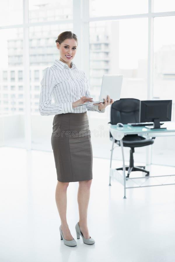 Ελκυστική χαμογελώντας επιχειρηματίας που κρατά το σημειωματάριό της στεμένος στο γραφείο της στοκ φωτογραφίες
