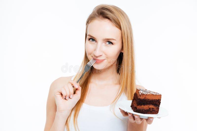 Ελκυστική χαμογελώντας νέα γυναίκα που τρώει το κομμάτι του κέικ σοκολάτας στοκ φωτογραφία με δικαίωμα ελεύθερης χρήσης
