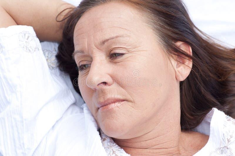 Λυπημένη συλλογιμένος ώριμη γυναίκα που στηρίζεται στο κρεβάτι στοκ εικόνα με δικαίωμα ελεύθερης χρήσης