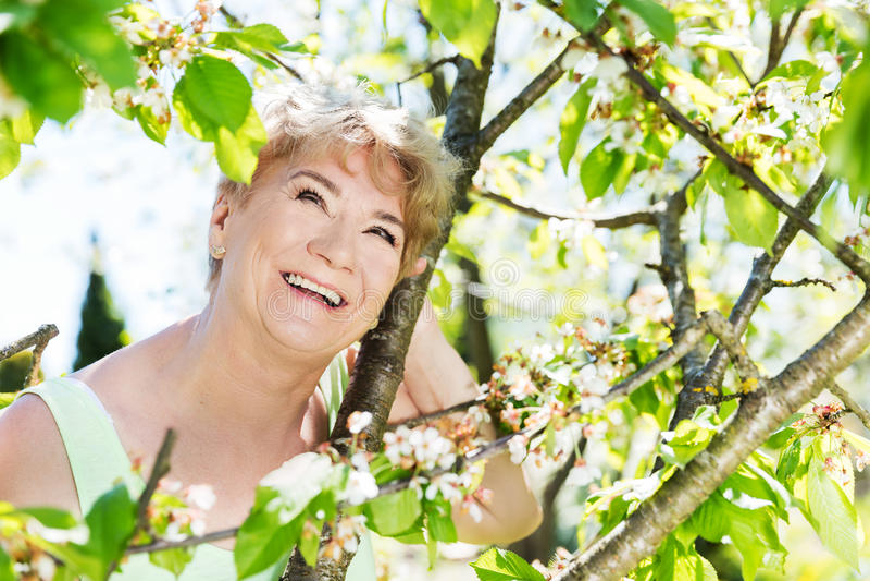 Ελκυστική ώριμη γυναίκα που αγκαλιάζει τη φύση γιαγιά στοκ φωτογραφίες