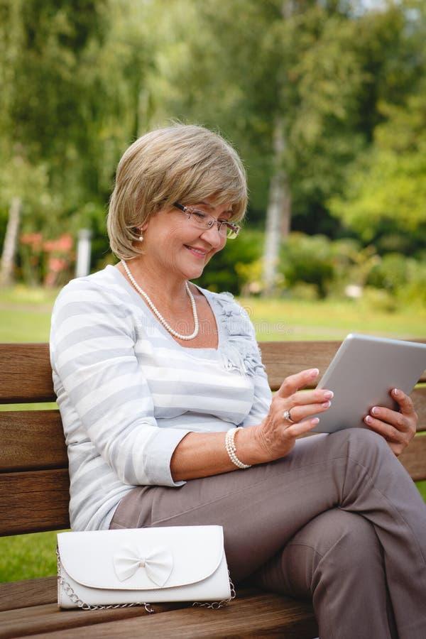 Ελκυστική ώριμη γυναίκα που χρησιμοποιεί την ψηφιακή ταμπλέτα σε ένα πάρκο στοκ φωτογραφία με δικαίωμα ελεύθερης χρήσης