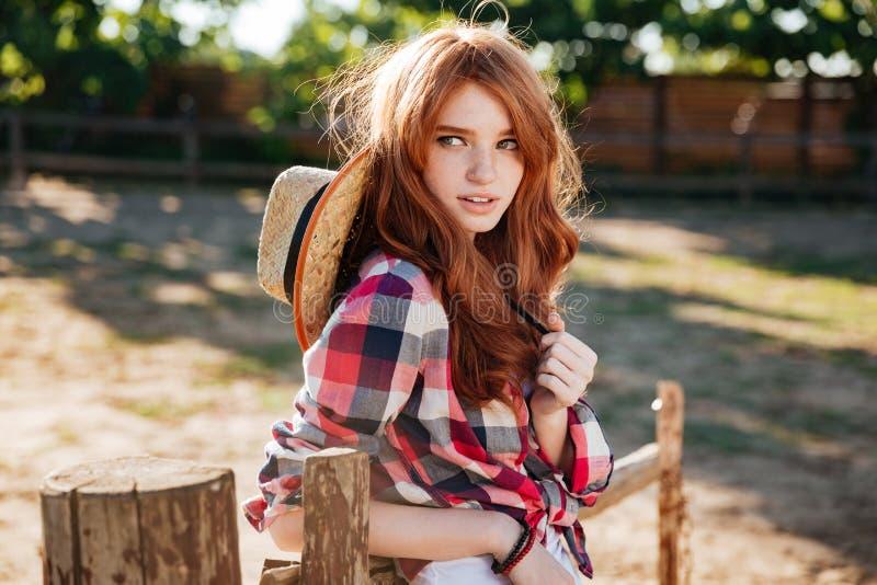 Ελκυστική redhead νέα γυναίκα cowgirl που στέκεται υπαίθρια στοκ εικόνες