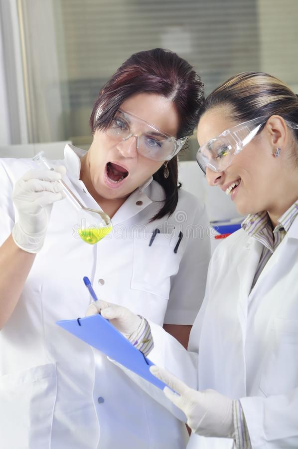 Ελκυστικοί νέοι επιστήμονες σπουδαστών PHD που παρατηρούν τη μετατόπιση χρώματος μετά από το destillation λύσης στο χημικό εργαστ στοκ φωτογραφίες με δικαίωμα ελεύθερης χρήσης