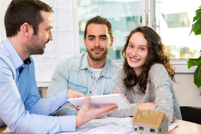 Ελκυστικοί νέοι που συναντούν το κτηματομεσίτη στο γραφείο στοκ εικόνα με δικαίωμα ελεύθερης χρήσης