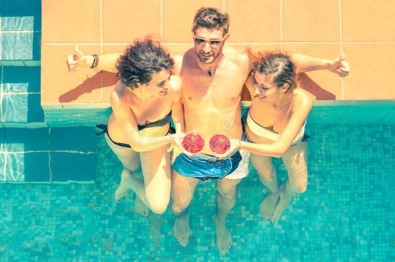Ελκυστικοί νέοι φίλοι που έχουν τη διασκέδαση σε μια πισίνα στοκ εικόνα με δικαίωμα ελεύθερης χρήσης