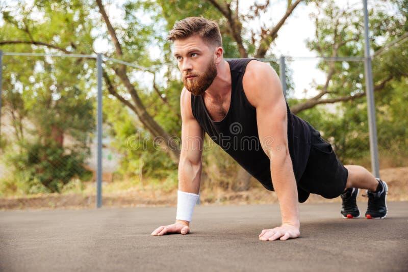 Ελκυστικός γενειοφόρος αθλητικός τύπος που κάνει το ώθηση-UPS υπαίθρια στοκ φωτογραφίες με δικαίωμα ελεύθερης χρήσης