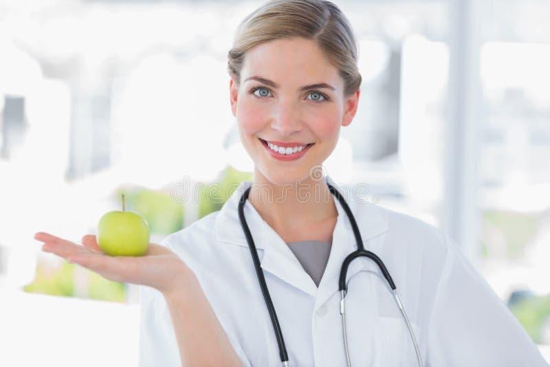 Ελκυστικός γιατρός γυναικών που παρουσιάζει ένα μήλο στοκ εικόνες με δικαίωμα ελεύθερης χρήσης