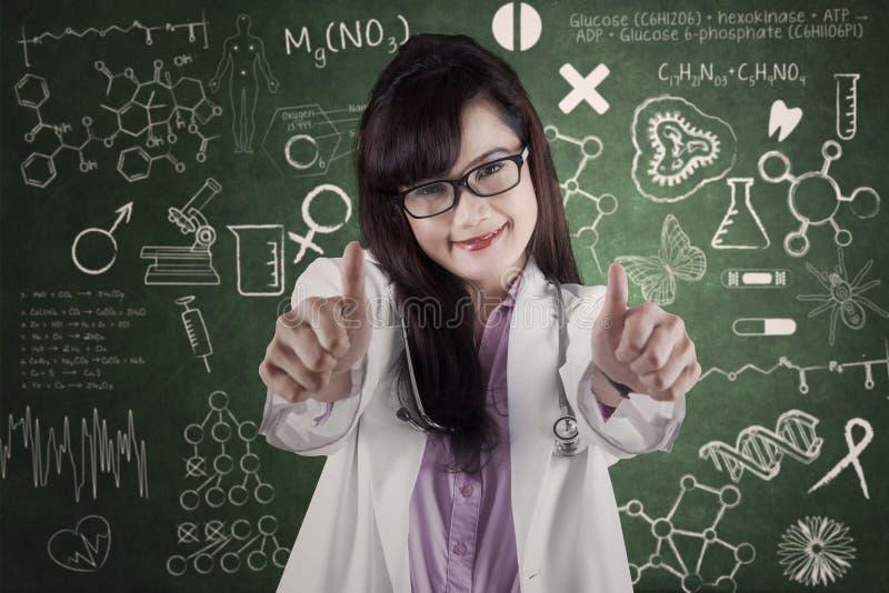 Ελκυστικός γιατρός που παρουσιάζει αντίχειρας-επάνω σε 2 στοκ εικόνες