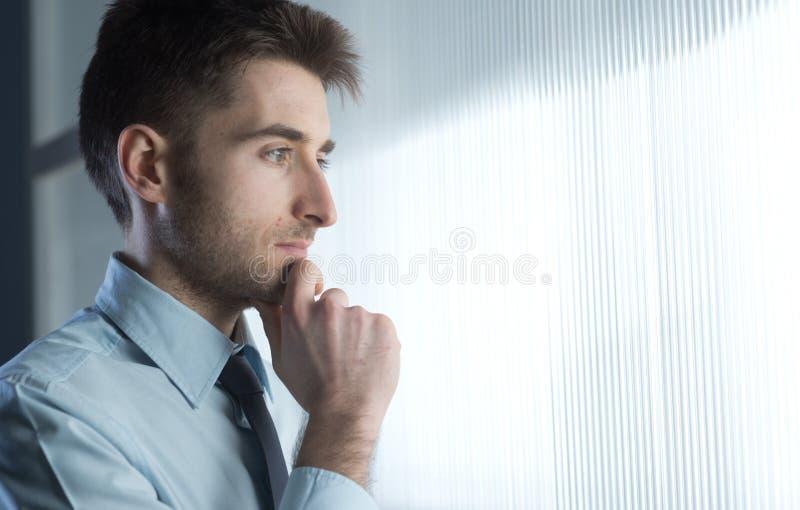 Ελκυστικός επιχειρηματίας στο παράθυρο στοκ φωτογραφίες