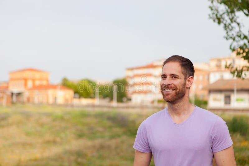 Ελκυστικός ευτυχής τύπος με τη γενειάδα και την πορφυρή μπλούζα στοκ φωτογραφία