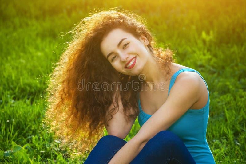 Ελκυστικός, νέο κορίτσι με τη σγουρή συνεδρίαση τρίχας στην πράσινη χλόη στο χορτοτάπητα και χαμόγελο στο φωτογράφο στοκ φωτογραφίες