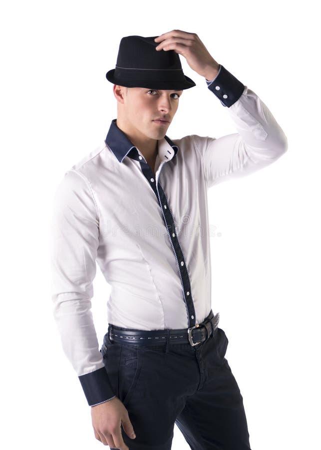 Ελκυστικός νεαρός άνδρας με το fedora και το άσπρο πουκάμισο στοκ φωτογραφία