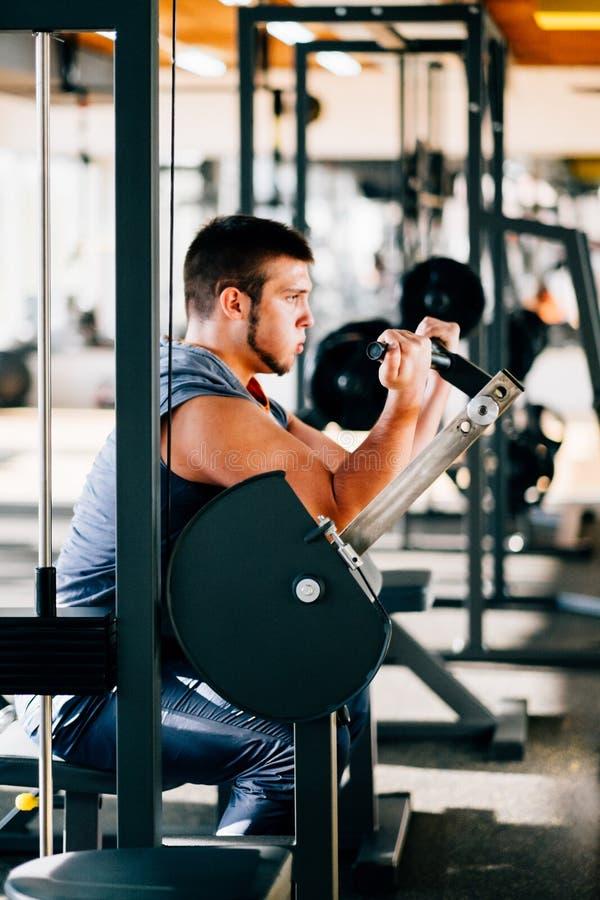 Ελκυστικός νεαρός άνδρας που κάνει τη βαρέων βαρών άσκηση για τους δικέφαλους μυς στη μηχανή σε μια γυμναστική στοκ εικόνες