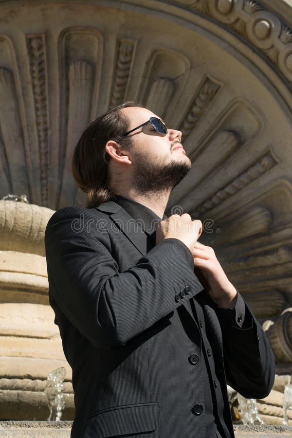 Ελκυστικός νεαρός άνδρας που ρυθμίζει το δεσμό του στοκ φωτογραφία με δικαίωμα ελεύθερης χρήσης